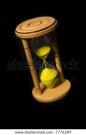 Wood hour glass with yellow sand isolated on black background - stock photo