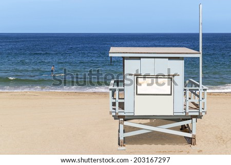 Wood lifeguard tower facing the ocean with male person paddle boarding in background. Focus on lifeguard hut. Motion blur of person and paddleboard. Gentle waves, clear blue sky background.  - stock photo