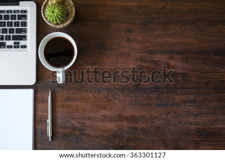 Wood office desk table with laptop, a cup of coffee and supplies. Top view with copy space. - stock photo