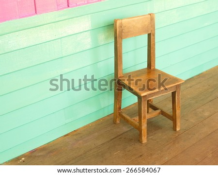 wood old kid chair in front of colorful pink and vintage blue wall - stock photo
