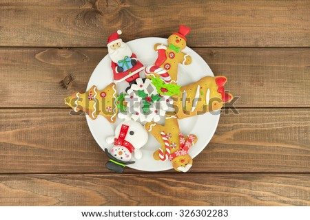 wood on a white plate background Christmas tree cookies, santa, middle-aged man, snowman, snowflake, candy. New year food - stock photo
