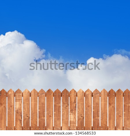 Wood picket fence with blue sky background - stock photo