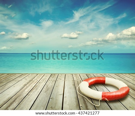 Wood pier with ocean and life preserver and blue sky in background - stock photo