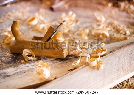 Wood planer, wooden planks and shavings at carpenters workshop - stock photo