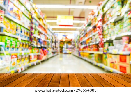 wood plank over blurred image of supermarket people shopping - product shelf - business concept - stock photo