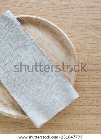 Wood plate with Napkin on the table - stock photo