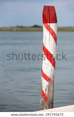 Wood post, pole, of venice port. Italy. Decorated wood post. - stock photo
