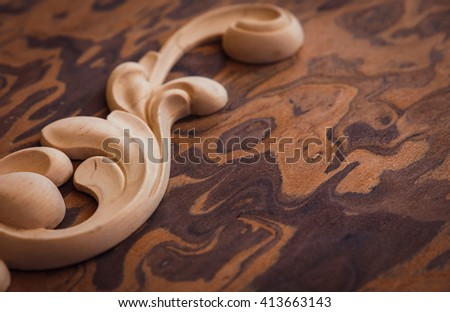 Wood processing. Joinery work. woodcarving. piece carved detail on a wooden background in perspective. close up. used as background. small depth of field - stock photo