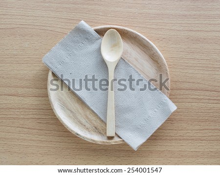 Wood spoon with Napkin on wood plate - stock photo
