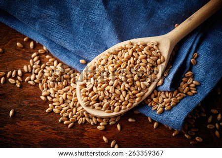 Wood spoon with whole wheat grains - stock photo