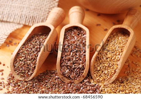 Wood spoons with whole brown, golden and ground flax seeds - stock photo