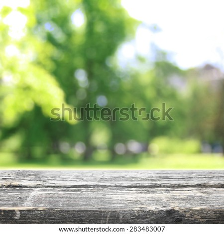 Wood table empty for object on sunny summer park - stock photo