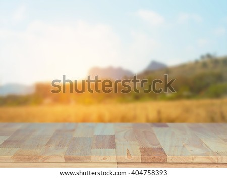 Wood table on meadow mountain sunrise nature countryside scenery - blur background - stock photo
