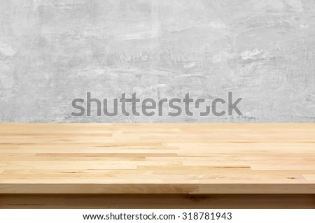 Wood table top on bare concrete wall background - can be used for display or montage your products - stock photo