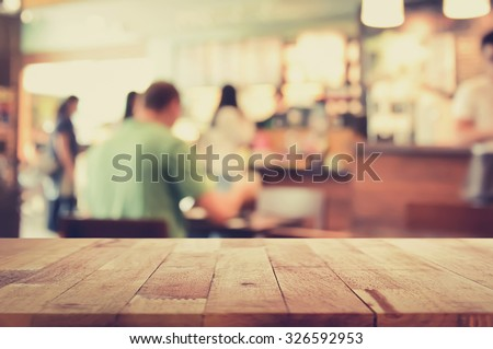 Wood table top on blur background of coffee shop interior with some people, vintage tone - can be used for display or montage your products - stock photo