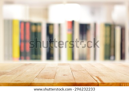 Wood table top on blur bookshelf background - can be used for display or montage your products - stock photo