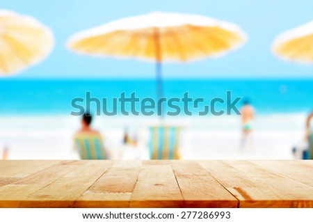 Wood table top on blurred beach background - can be used for montage or display your products - stock photo