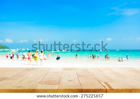 Wood table top on blurred beach background with people in colorful clothes - can be used for display or montage your products - stock photo