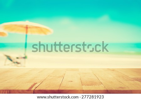 Wood table top on blurred blue sea and white sand beach background, vintage tone - can be used for display or montage your products - stock photo