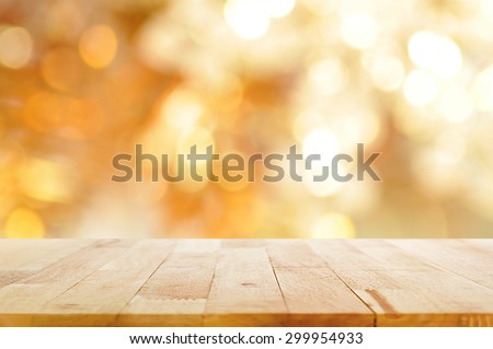 Wood table top on shiny bokeh gold background - can be used for display or montage your products - stock photo