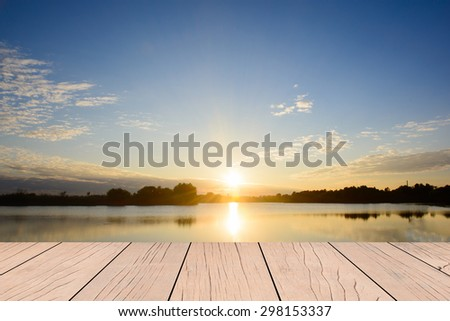 Wood table top on sunrise in the sea background - stock photo