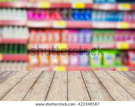 wood table with detergent shelves in supermarket or grocery store blurred background - stock photo