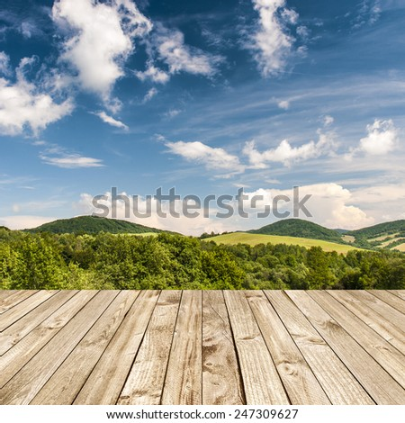Wood terrace and perspective view on forest hills - stock photo