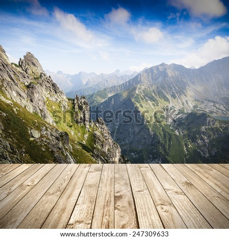 Wood terrace and perspective view on high mountains - stock photo