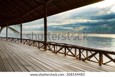 wood terrace in wooden pavillion against peaceful of heaven sea beach - stock photo