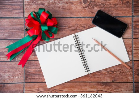 Wood texture mock up with notebook, ribbon, smart phone and pencil. View from above.Create a card. - stock photo