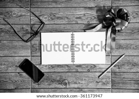 Wood texture mock up with notebook, ribbon, smart phone , glasses and pencil. View from above.Create a card. Black and white. - stock photo