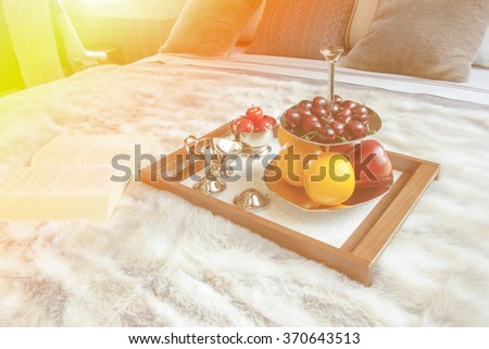 WOOD Tray with FRUITS on a bed in a hotel room - stock photo