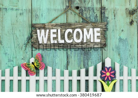 Wood welcome sign hanging over white picket fence with spring flower and colorful butterfly on antique rustic mint green wooden background - stock photo