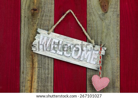 Wood welcome sign with red and white candy cane striped heart hanging on antique red and wooden rustic background - stock photo