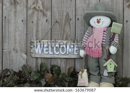 Wood welcome sign with snowman in green overalls with garland border - stock photo