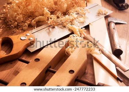 Wood working desk near the window with incandescent  lighting, Wood working tools and wood shavings.  - stock photo