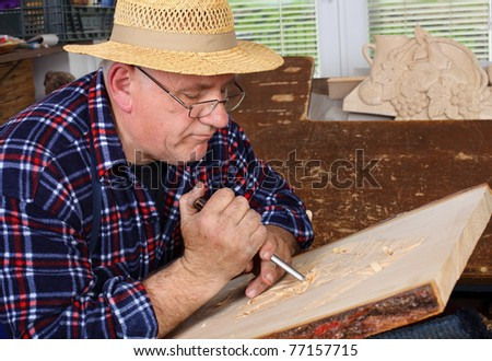 Woodcarver work in his workshop. - stock photo