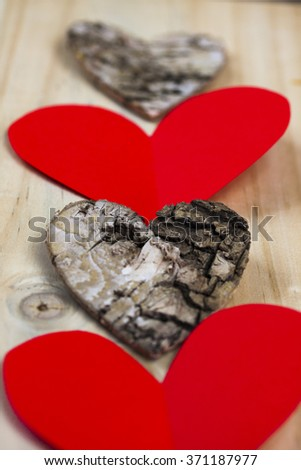 Wooden and paper hearts on wooden background - stock photo