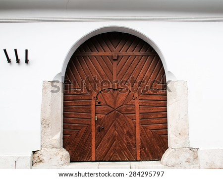 Wooden arch door at white old building - stock photo