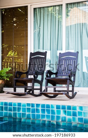 Wooden arm chairs beside the pool, stock photo - stock photo