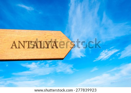 Wooden arrow sign pointing destination ANTALYA, TURKEY against clear blue sky with copy space available. Travel destination conceptual image - stock photo