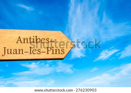 Wooden arrow sign pointing destination Antibes-Juan-les-Pins, FRANCE against clear blue sky with copy space available. Travel destination conceptual image - stock photo