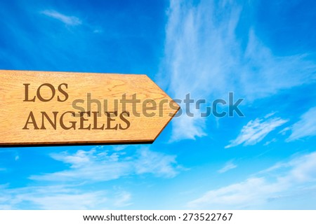 Wooden arrow sign pointing destination LOS ANGELES    against clear blue sky with copy space available. Travel destination conceptual image - stock photo