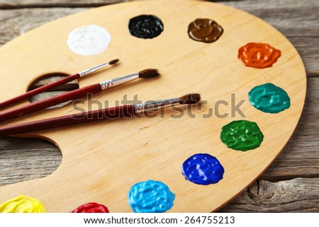 Wooden art palette with paints on grey wooden background - stock photo