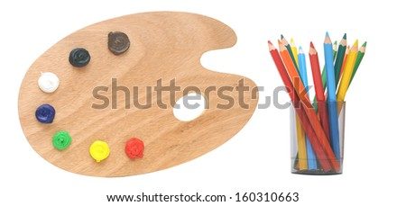 wooden artists palette loaded with various color paints and colorful pencils isolated on a white background - stock photo