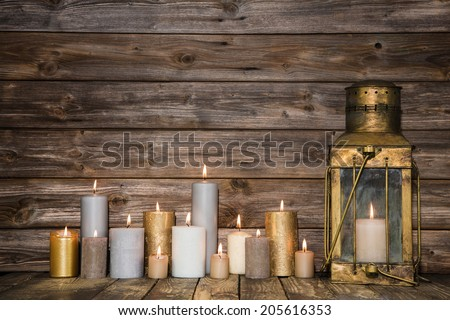 Wooden background in with many burning candles and a old rustic lantern. - stock photo