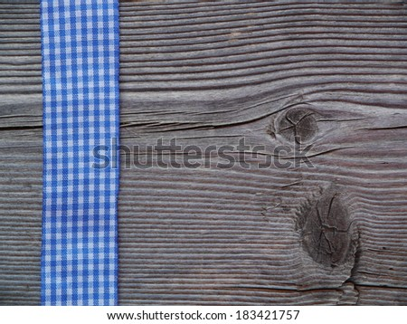 wooden background with a blue checked ribbon - stock photo