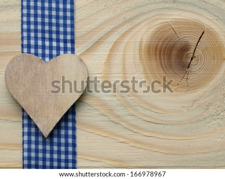 wooden background with a blue checked ribbon and a heart - stock photo