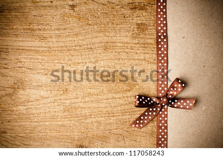 Wooden background with brown polka-dot ribbon and bow on brown kraft paper - stock photo
