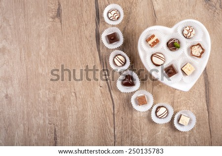 Wooden background with chocolate pralines, text space, focus on the chocolates in the heart-shaped plate - stock photo